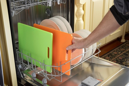 Placing colored cutting boards into the dishwasher