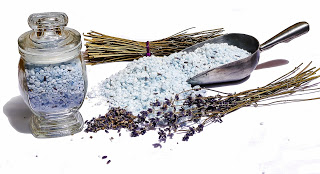 Epsom salts in a jar next to a metal scoop of Epsom salts and dried lavender scattered on a table.