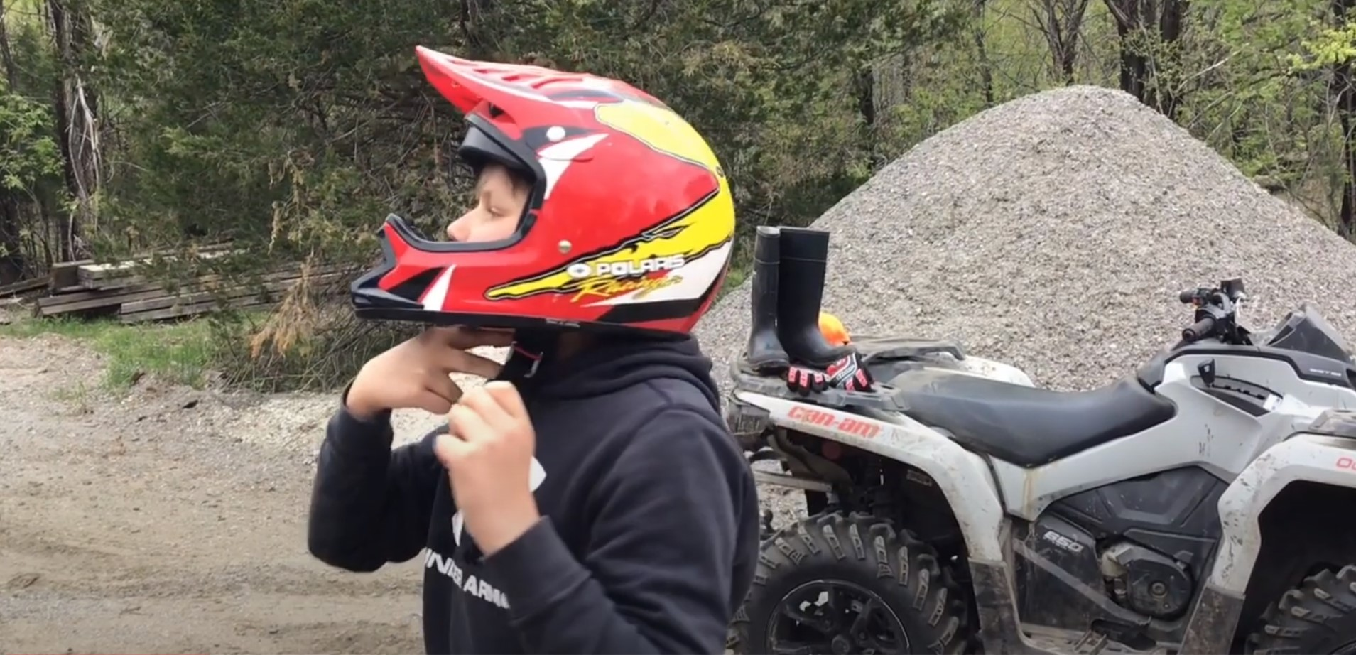 Boy wearing a red helmet standing in front of his ATV as he shows how to adjust strap