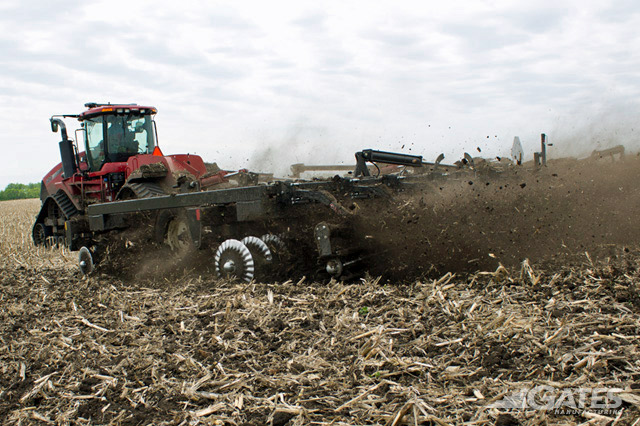 Red tractor pulling tillage equipment in a harvested field and debris in the air behind the equipment.