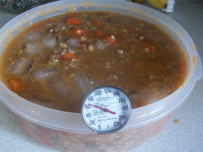 Cooling soup with thermometer.