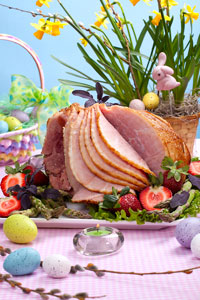 Easter ham on platter with eggs around.