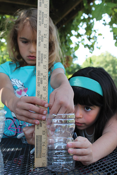 Two girls measuring a plastic bottle with a yardstick