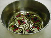 Pot of jar lids in a pan with water.