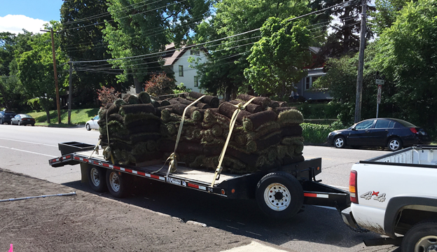 A truck and trailer with rolls of sod next to a boulevard of bare soil