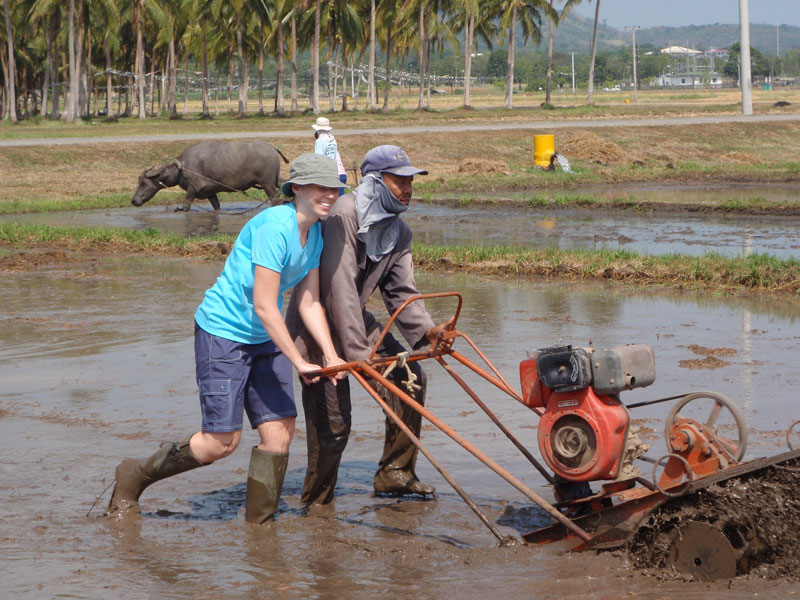 two people pushing a piece of equipment through a muddy, shim deep, pool of water.