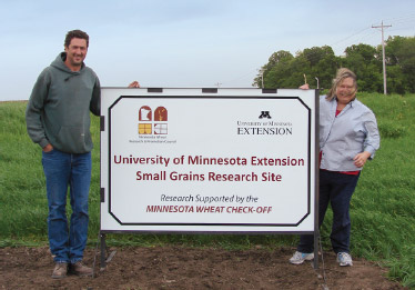 Educator and farmer holding sign about on-farm research