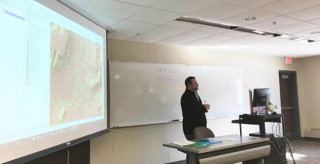 Joel Larson standing in front of a projection screen showing a LiDAR map while teaching a class.