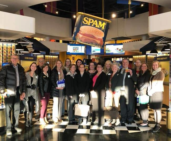 Group of adults gathered for a group picture standing under a large can of SPAM.