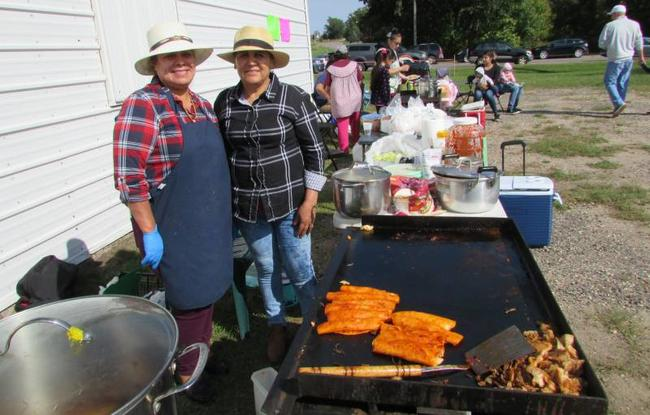 Two women standing behind a large flat top grill cooking food.