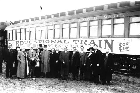 Education train from early 1900s with 15 men and women in front of it