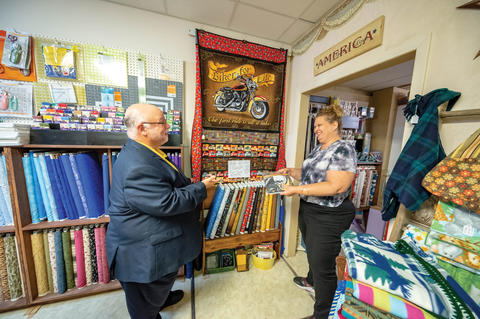 Man visiting quilt shop and talking with owner. Different fabrics are on the wall behind the two people.