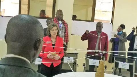 Catie Ramsmussen leads a group of Kenyans in a leadership experience involving string symbolizing networks and connections