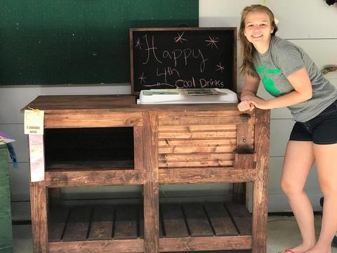 4-H youth standing next to a wooden sideboard