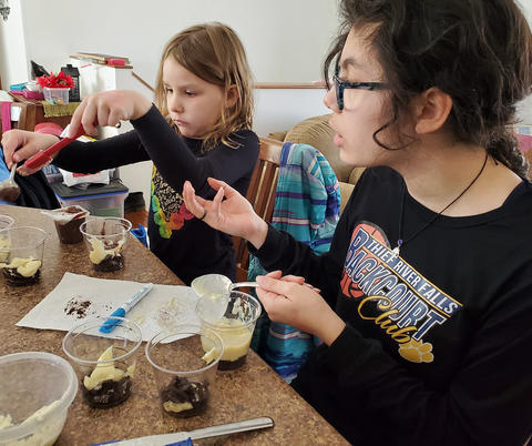 Two girls doing at-home 4-H activity
