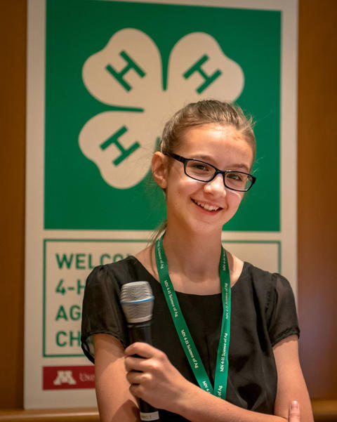 4-H ag ambassador with a microphone.
