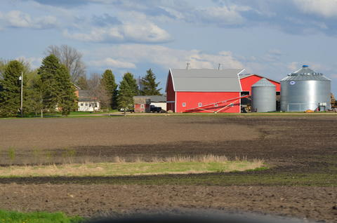 Farmstead with large field in foreground and red barn in the distance.
