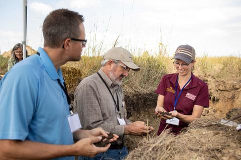 Anna in soil pits with two class participants looking at soils