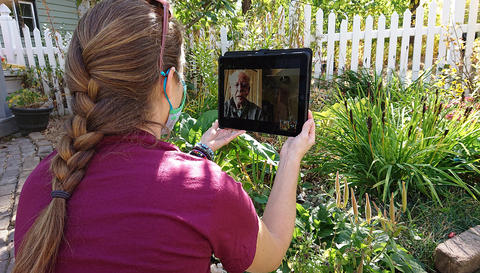 Woman in a garden looking at an iPad talking to older man and showing him the garden.