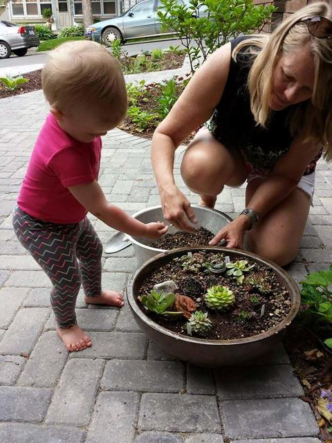 Woman and toddler planting a rock garden in a container.