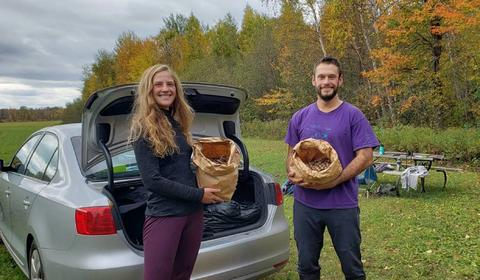 Kelly Popham and Joel Bransky holding bags of collected acorns with woods in the background.