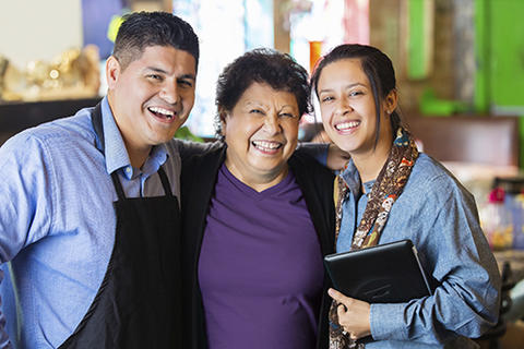 Three Latino adults smiling