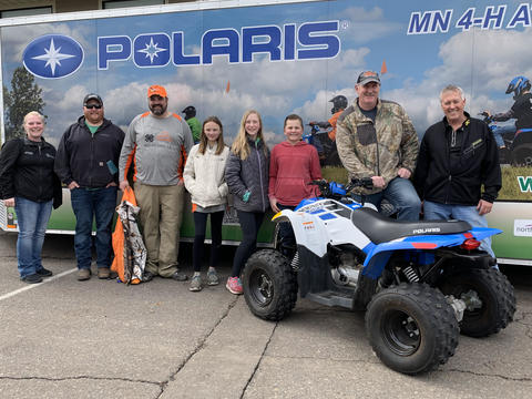 Eight people in front of Polaris 4-H trailer with ATV