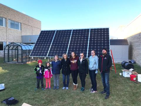 Students and teachers standing in front of a ground mounted solar panel.