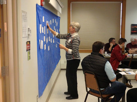 Linda Kingery adding notes to a sticky board during a community meeting.
