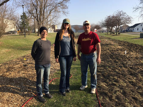 Veronica Shukla, Kimberly Rockman and Gary Wyatt standing on grass next to a row of plantings for the Food Forest.
