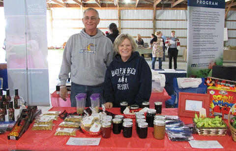 A man and woman standing together behind a table loaded with homemade products they are selling at Salsa Fest.