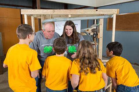 Volunteers and 4-H'ers working on Rube Goldberg project