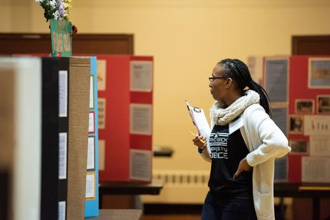 female scientist looks over project poster boards with a clipboard in hand