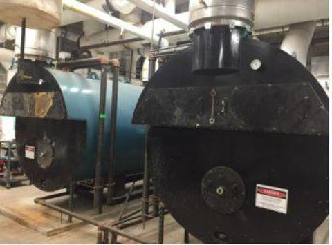 Two commercial boilers sitting side by side in a mechanical room.