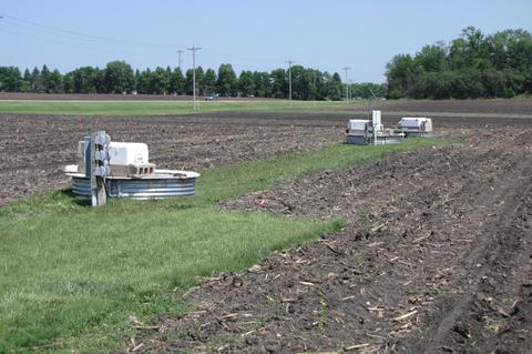 plowed soil with patch of grass where water drainage equipment is located.