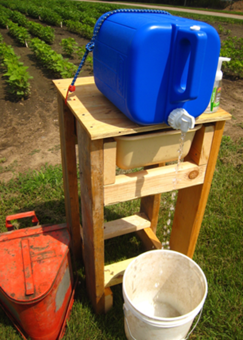 Example of a build-your-own handwashing station. Tank with water sitting over a bucket in a farm field.