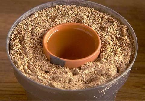 A large plastic pot filled with vermiculite with a water-filled clay pot in the center of the vermiculite.