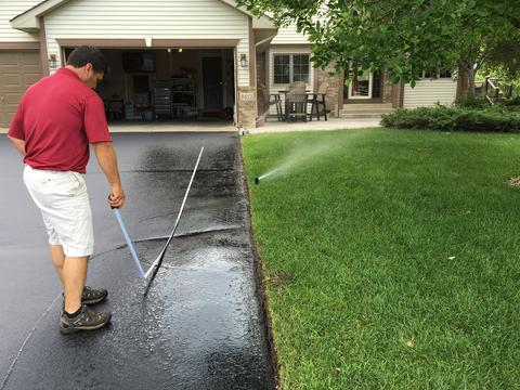 A person in a suburban yard measuring misdirected irrigation spray on a driveway.