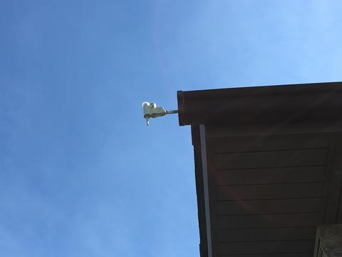 Rain gauge attached to a home's roof.