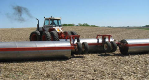 Tractor pulling equipment that has three large metal rollers and two sets of wheels.