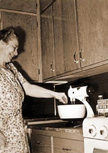 Woman using electric mixer in her home