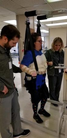 Anna strapped in a machine to help her relearn to walk with a therapist on each side of her.