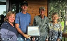 Four members of the Jutsen family of Cedar Drive Stock Farm show their Farm Family certificate
