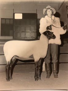 Black and white photo of Diane Kennedy with a goat.