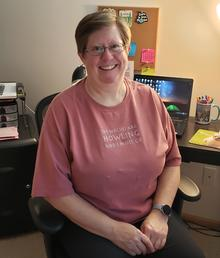 Kathy Kneeland in her office. She is smiling at the camera.