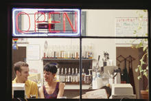 Open sign in a cafe with people