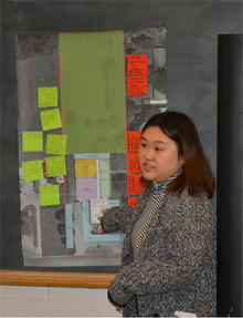 Khou Lor standing in from of a board with notes of ideas as she facilitates a community feedback session