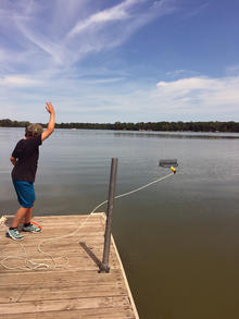 William Guthrie throwing a rake into the water off of the end of a dock.