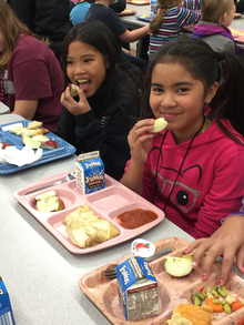 Two elementary student eat a healthy lunch including Minnesota grown apples.