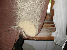 Curtain hanging from window, draped over chair arm, covered in sawdust